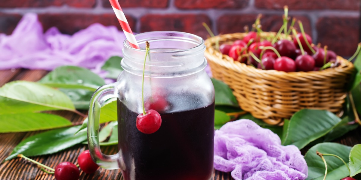 Photo of a basket of cherries and a glass mug of cherry juicer for a Cherry Juice Recipe